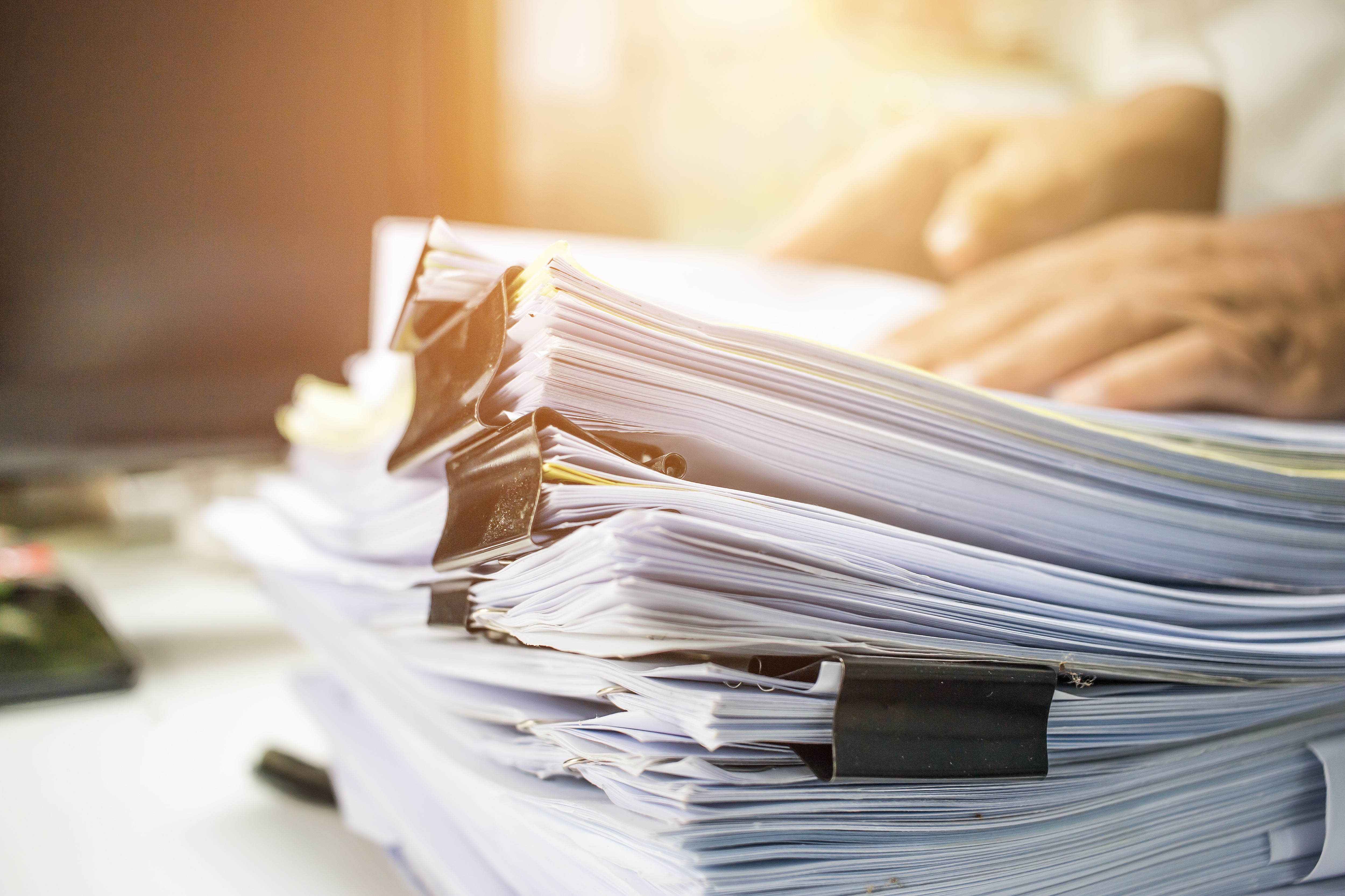 A large stack of papers with binder clips